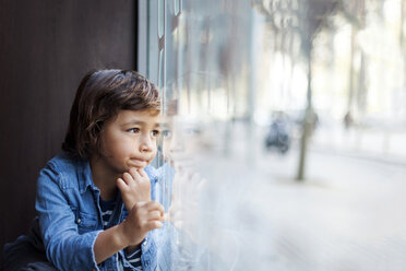 Portrait of little boy looking through window display - VABF000010
