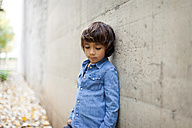 Portrait of sad little boy wearing denim shirt leaning against concrete wall - VABF000022