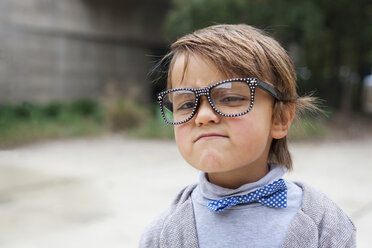 Portrait of little boy wearing oversized spectacles and boy tie making funny face - VABF000025