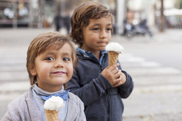 Portrait of happy little with ice cream cone and his brother in the background - VABF000028