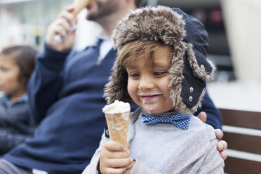 Portrait of happy little boy with ice cream cone sitting besides his father on a bench - VABF000031