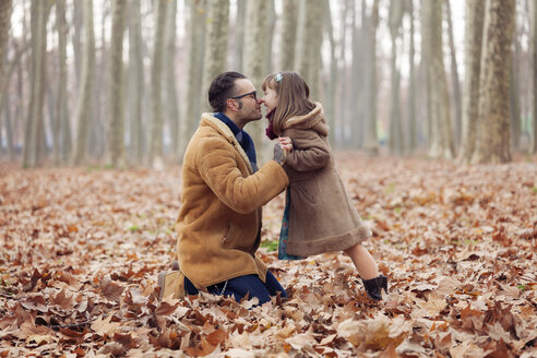 Father kissing his daughter in park, autumn - XCF000050
