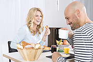 Happy couple having breakfast at hoome - MAEF011131