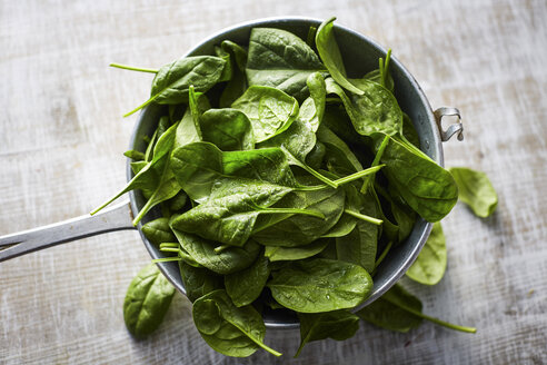 Fresh spinach leaves in colander on wood - KSWF001718
