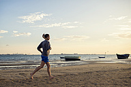 Spain, Puerto Real, woman jogging on the beach at evening twilight - KIJF000041