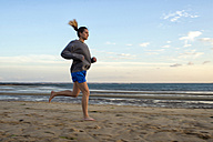 Spain, Puerto Real, woman jogging on the beach at evening twilight - KIJF000044