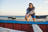 Spain, Puerto Real, young woman doing stretching exercices on the beach - KIJF000047