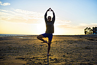 Spain, Puerto Real, silhouette of young woman doing yoga on the beach at sunset - KIJF000050