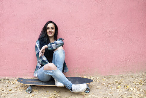 Portrait of smiling young woman sitting on longboard in front of pink wall - KIJF000053
