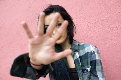 Young woman in front of pink wall looking through her fingers - KIJF000056