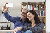 Smiling couple at home taking a selfie - RBF003638
