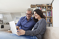 Smiling couple at home on couch using laptop - RBF003641
