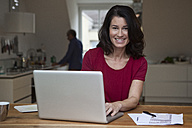 Smiling woman at home using laptop with man in background - RBF003647