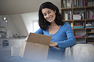 Smiling woman at home sitting on couch unpacking parcel - RBF003659