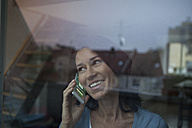 Smiling woman behind windowpane on cell phone - RBF003665