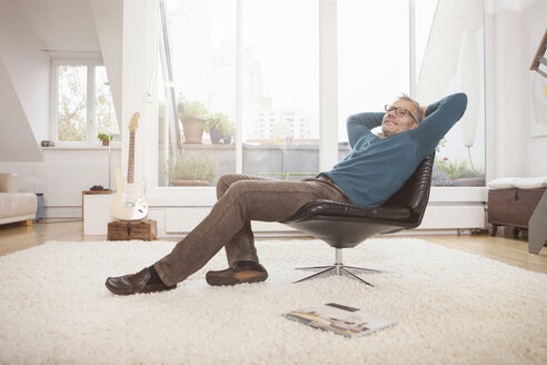 Relaxed mature man at home sitting in chair - RBF003680