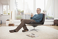 Smiling mature man at home sitting in chair looking at cell phone - RBF003683