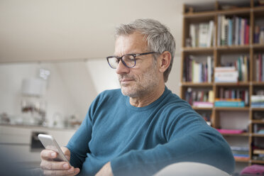 Mature man at home looking at cell phone - RBF003692