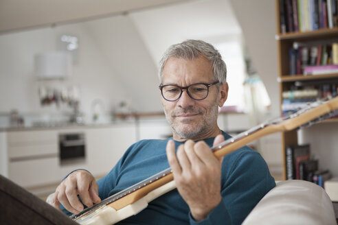 Mature man at home playing guitar - RBF003695