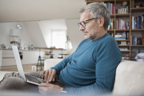 Mature man at home sitting on couch using laptop - RBF003698