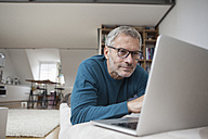 Mature man at home lying on couch using laptop - RBF003701