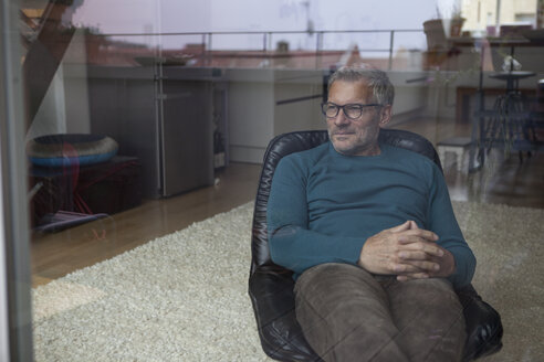 Mature man sitting behind windowpane looking out - RBF003710