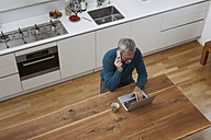 Mature man in kitchen with cell phone and laptop - RBF003722