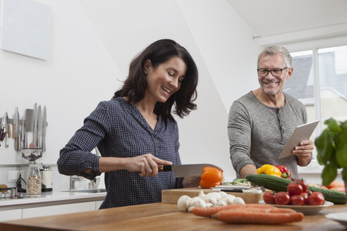 Mature couple with digital tablet cooking in kitchen - RBF003725