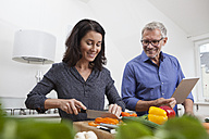 Mature couple with digital tablet cooking in kitchen - RBF003728
