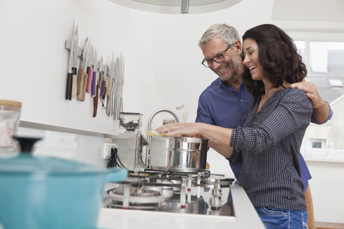 Mature couple cooking spaghetti in kitchen - RBF003737