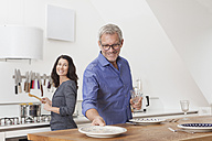 Mature couple cooking in kitchen with woman cooking and man laying the table - RBF003746