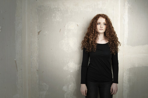 Portrait of serious looking redheaded teenage girl in front of concrete wall - GDF000945