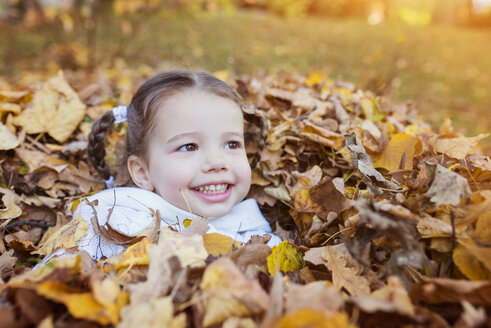 Happy girl sinking in autumn leaves - HAPF000064