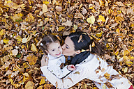 Mother kissing daughter in autumn leaves - HAPF000067
