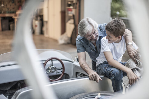 Grandfather and grandson restoring a car together - ZEF007632
