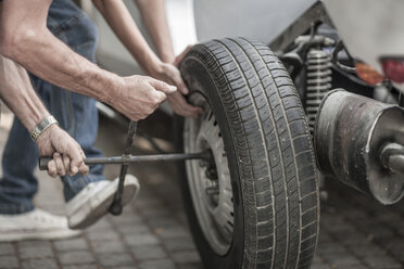 Grandfather and grandson changing car tire - ZEF007638