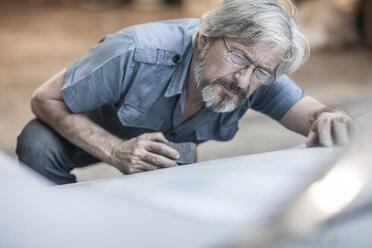 Senior man scrutinizing car - ZEF007641