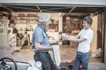 Grandfather and grandson having a break from restoring a car - ZEF007644