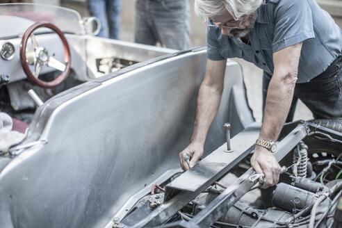 Senior man restoring a car - ZEF007647