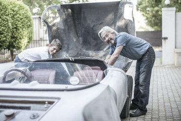 Grandfather and grandson restoring a car together - ZEF007650