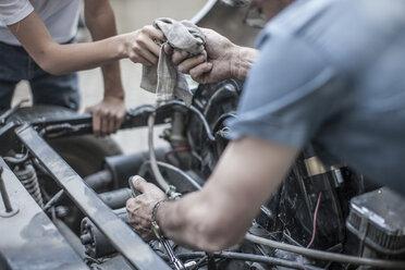 Grandfather and grandson restoring a car together - ZEF007653