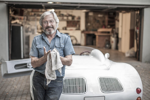 Smiling senior man with cleaning cloth leaning at sports car - ZEF007662