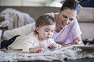 Mother and baby girl at home looking at book - ZEF007674