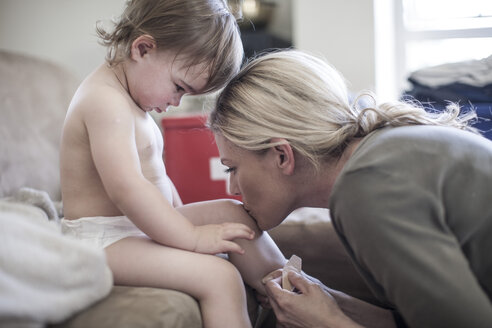 Mother and baby girl together at home putting on a plaster - ZEF007680