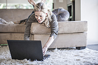 Woman lying on couch using laptop - ZEF007683