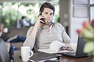 Man sitting at dining room table working at home - ZEF007698