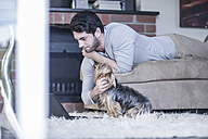 Man with dog lying on couch looking at laptop - ZEF007701