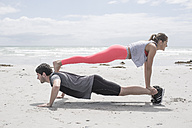 Young man and woman exercising on beach - ZEF007731