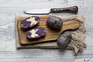 Sliced and whole purple potatoes on wooden board and cloth - SARF002404