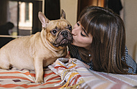 Young woman kissing her French bulldog sitting on the bed - GEMF000574
